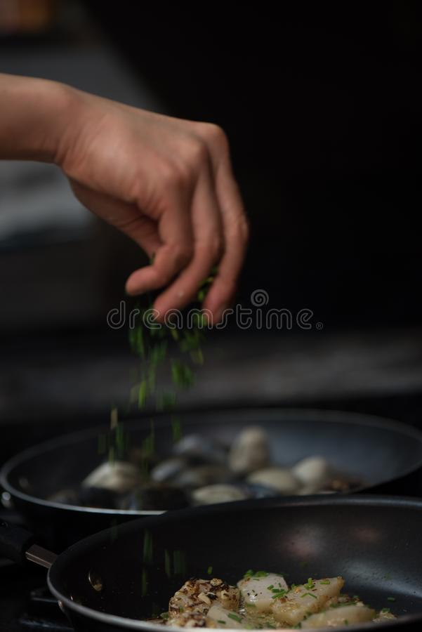 Vertical shot of a hand pouring spice on the potatoes in the pan with blurred background. A vertical shot of a hand pouring spice on the potatoes in the pan with royalty free stock photography