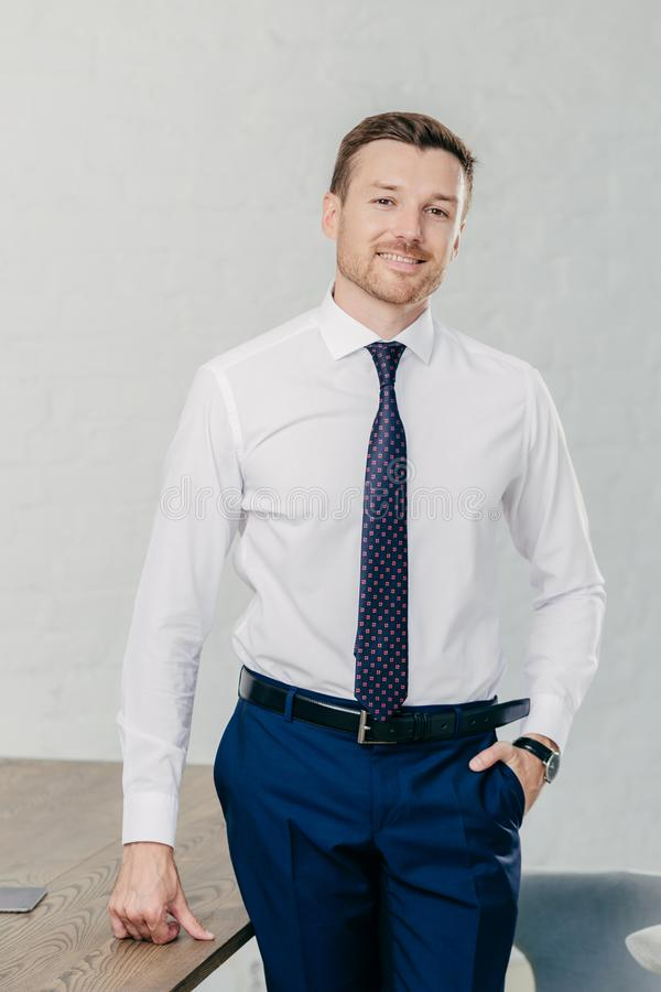 Vertical shot of handsome unshaven cheerful man wears formal clothes, keeps hand in pocket, stand near office table, has positive royalty free stock photography