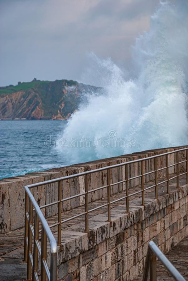 Vertical shot of harbor pier with waves crashing. In Comillas, Cantabria, Spain, Europe stock photos