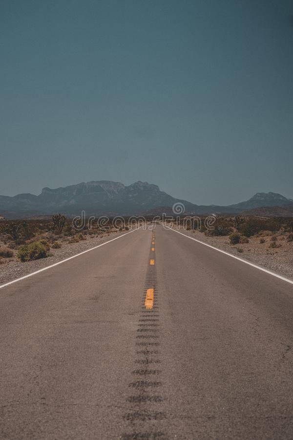 Vertical shot of a highway road going through the desert with mountains in the background stock photos