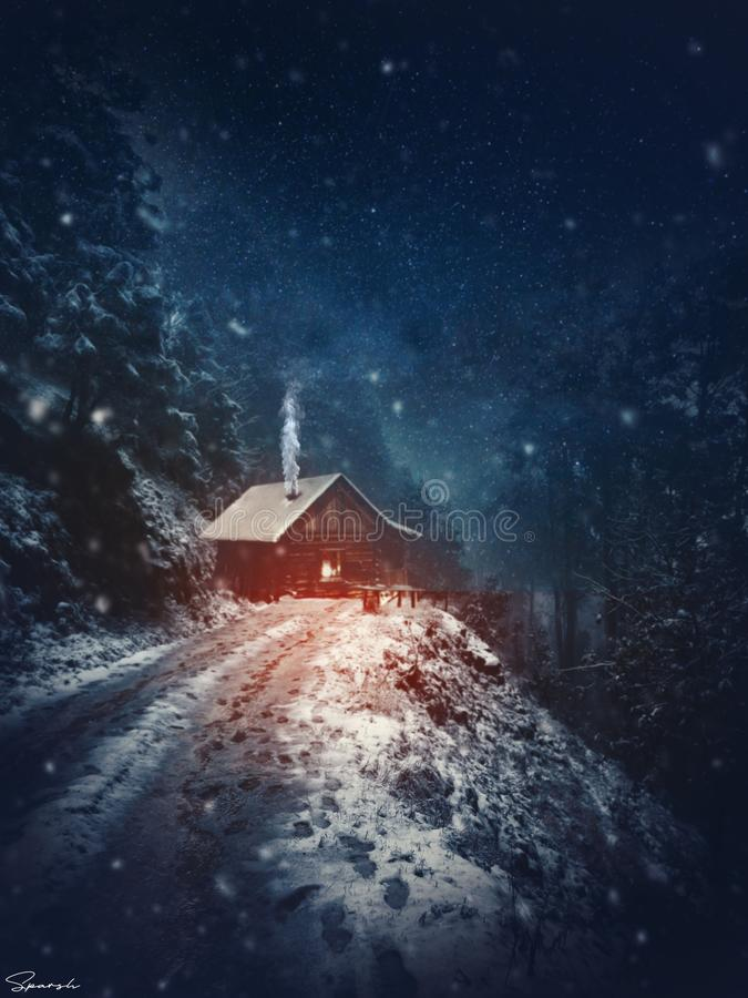 Vertical shot of a house on a snowy cliff with trees and a dark blue sky in the background. A vertical shot of a house on a snowy cliff with trees and a dark stock photos