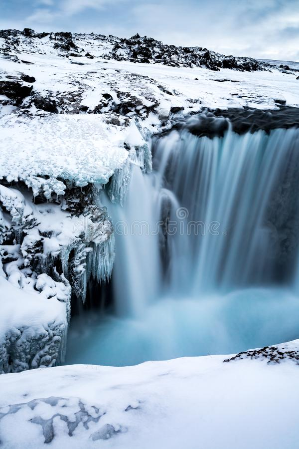 Vertical shot of Hranabjargafoss waterfall in Iceland. In winter royalty free stock photo