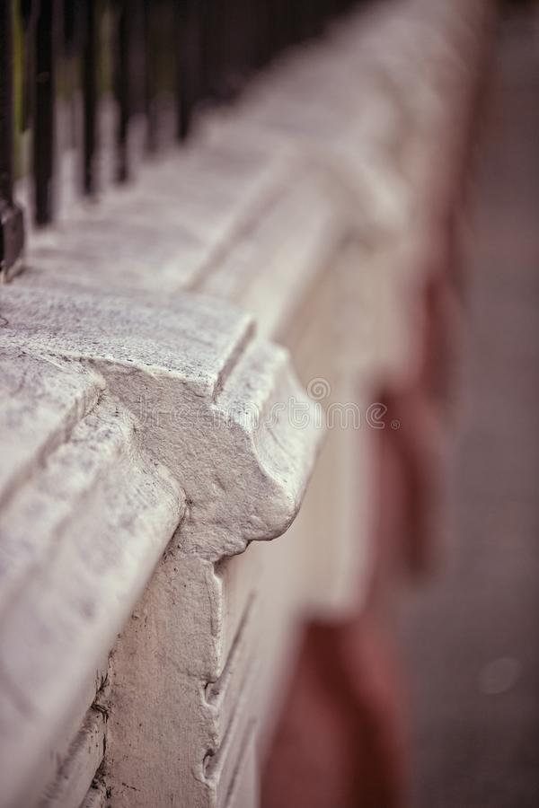 Vertical shot of an iron fence on wall and details with blurred background. A vertical shot of an iron fence on wall and details with blurred background stock photography