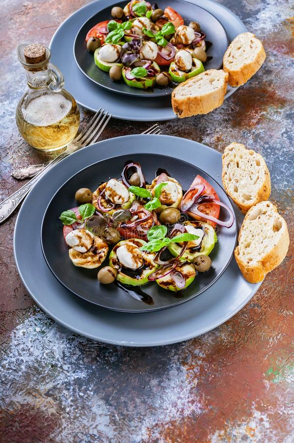 Vertical shot of italian salad with grilled vegetables, mozzarella cheese, olives, red onion, basil and balsamic sauce on a rust. Background. Mediterranean stock photography