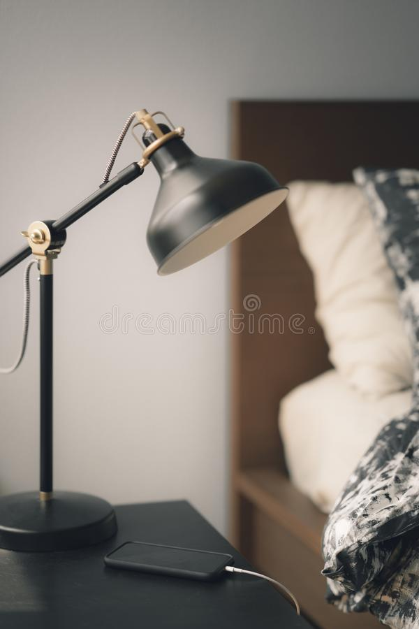 Vertical shot of a lamp and a charging smartphone on a table near the bed indoors. A vertical shot of a lamp and a charging smartphone on a table near the bed stock image