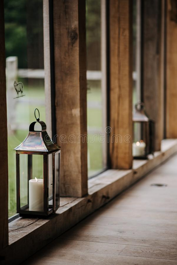Vertical shot of a lantern with a white candle in it on a wooden surface. A vertical shot of a lantern with a white candle in it on a wooden surface stock photos
