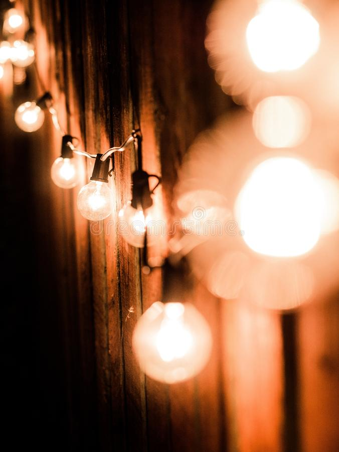 Vertical shot of lit lightbulbs on an electrical wire near a wooden fence royalty free stock photo