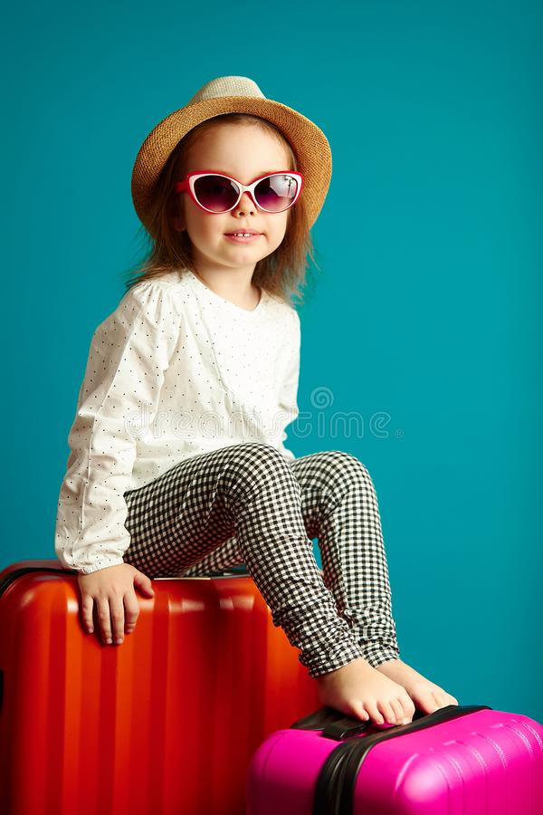 Vertical shot of little cute girl in straw hat and sunglasses sitting on suitcases, portrait of beautiful child going on. A journey, studio shot over blue royalty free stock image