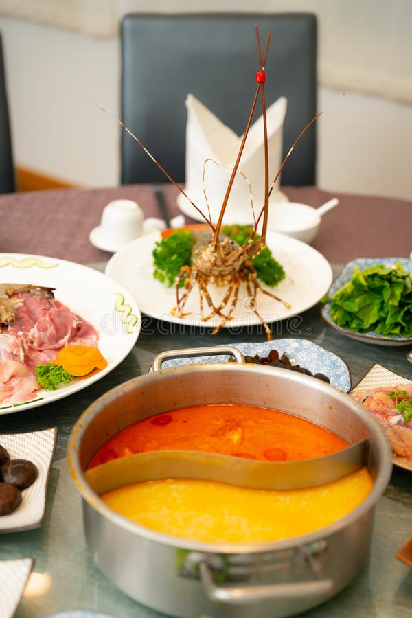 Vertical shot of a lobster near a soup with a side dishes. A vertical shot of a lobster near a soup with a side dishes stock photos