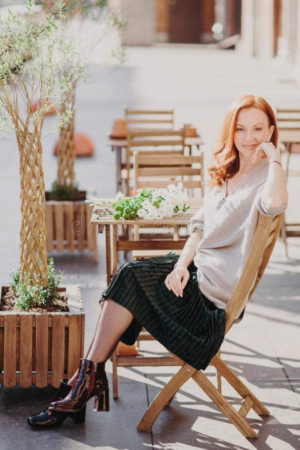 Vertical shot of lovely red haired woman sits on chair, waits for order in outdoor cafe, wears jumper, skirt and shoes, looks at royalty free stock image