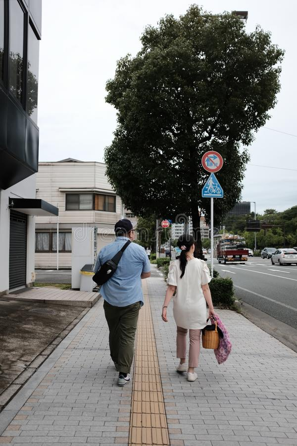 Vertical shot of a male and female walking along a sidewalk with houses and trees by the street stock image