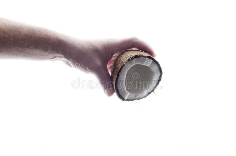 Concept of pouring coconut milk from fresh tasty coconut in male hand against whiet background stock image