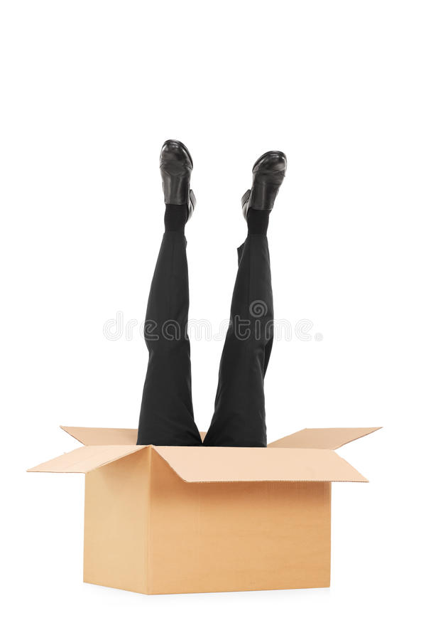 Vertical shot of male legs sticking out of a box. Isolated on white background royalty free stock photos