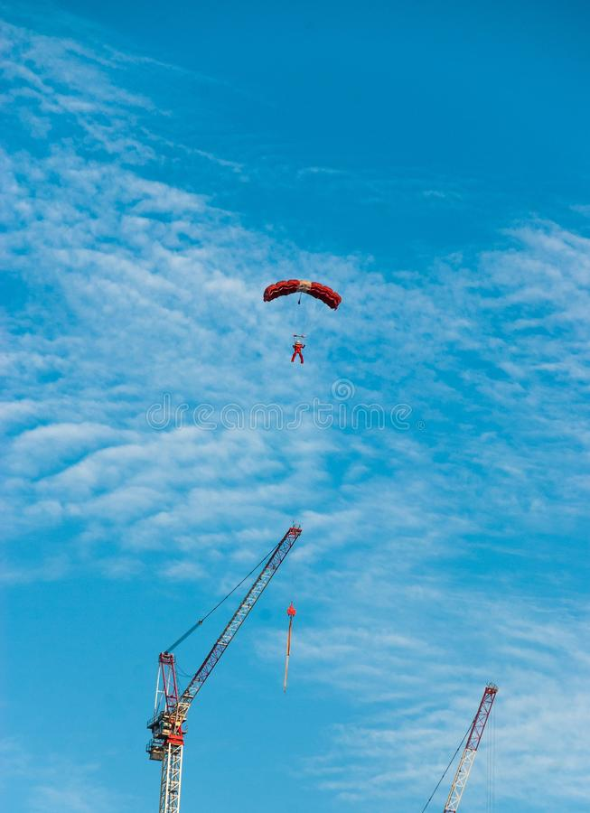Vertical shot of male parachuting with cranes and blue sky in the background. A vertical shot of male parachuting with cranes and blue sky in the background royalty free stock photography