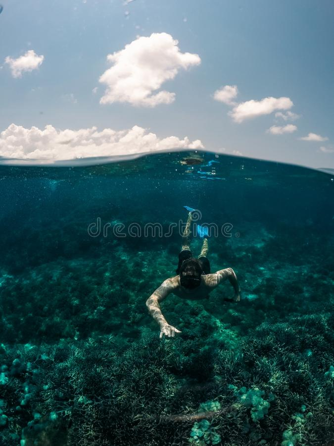 Vertical shot of male swimming underwater with the sky in the background. A vertical shot of male swimming underwater with the sky in the background stock photos