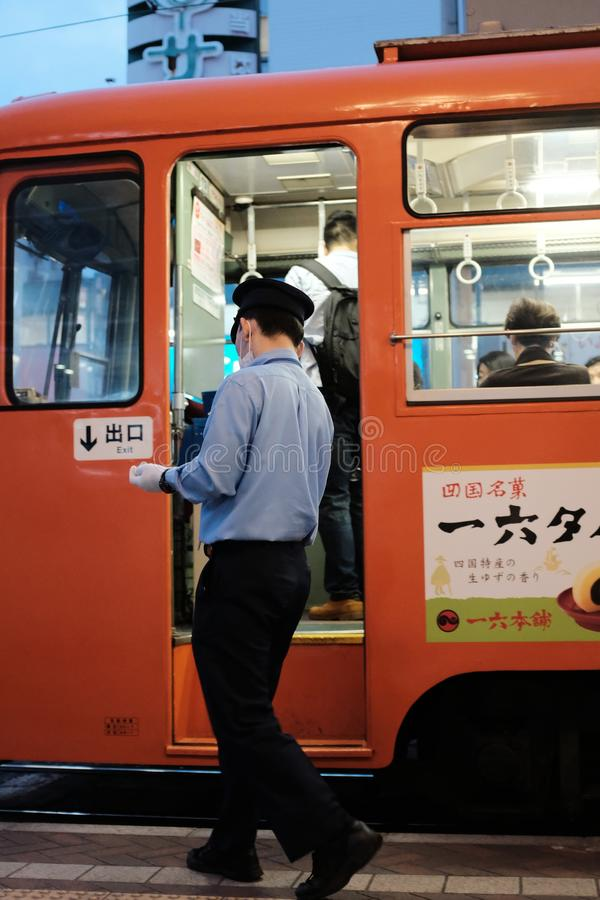 Vertical shot of a male wearing blue shirt and black pants standing near an orange bus. MATSUYAMA, JAPAN - Sep 21, 2019: A vertical shot of a male wearing blue royalty free stock photo