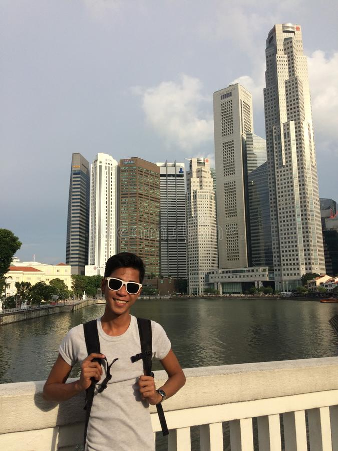 Vertical shot of a male wearing sunglasses standing near skyscrapers by the Singapore River stock photography