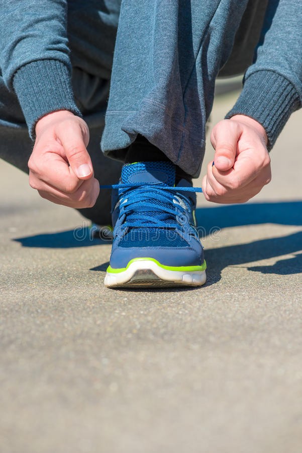Vertical shot of man tying a shoelace. Hands close-up royalty free stock images