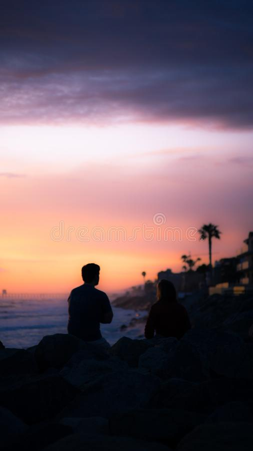 Vertical shot of a man and a woman sitting and talking near a body of water during sunset stock photo