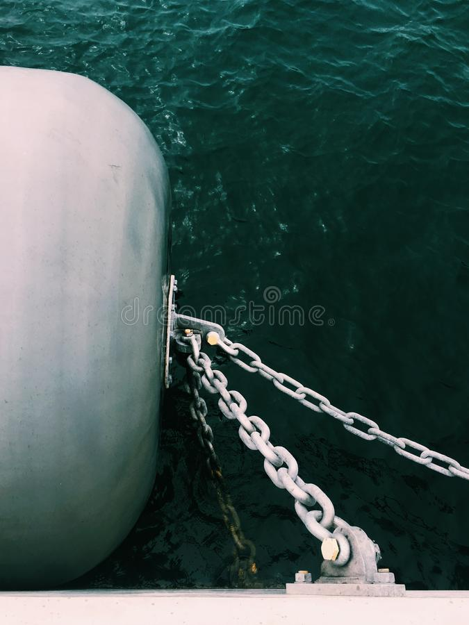 Vertical shot of metal chains connected to a barrel on a side of the boat. A vertical shot of metal chains connected to a barrel on a side of the boat royalty free stock photos
