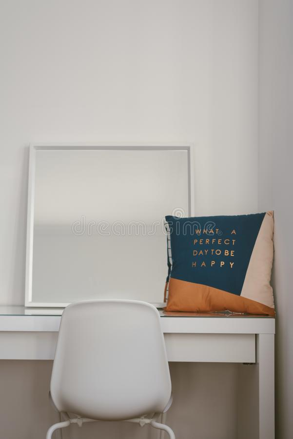 Vertical shot of a mirror and cushion on a white table with a chair in front stock photography
