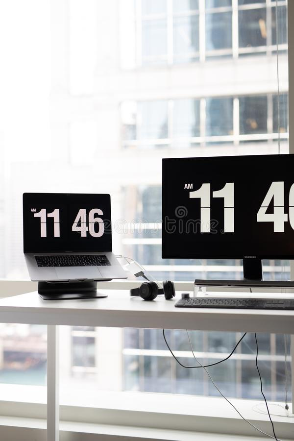 Vertical shot of a modern office desk with monitors showing the time and headphones. A vertical shot of a modern office desk with monitors showing the time and stock images