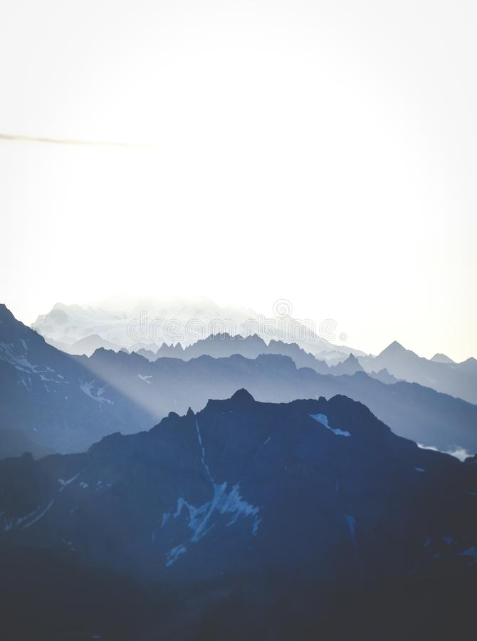 Vertical shot of mountains under a bright sky. A vertical shot of mountains under a bright sky royalty free stock images