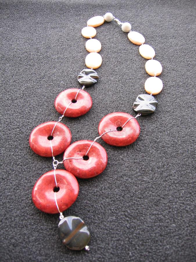 Vertical shot of a necklace made of white, red and black beads on a gray surface stock photos