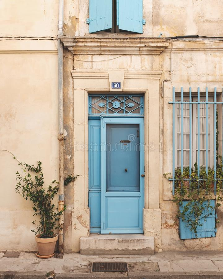 Free Vertical Shot Of An Old Building Facade With A Blue Entrance Door And Wooden Window Shutters Stock Photos - 161115103