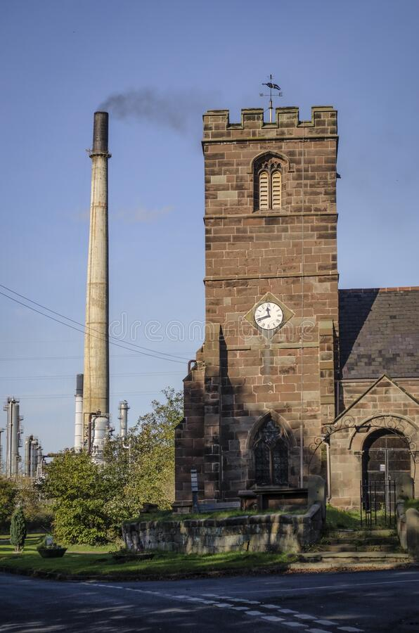 Vertical shot of an oil refinery chimney close to a village church in the UK. A vertical shot of an oil refinery chimney close to a village church in the UK royalty free stock image