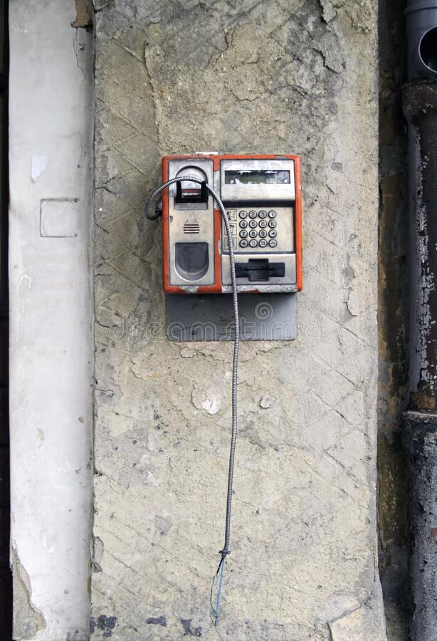 Vertical shot of an old broken public telephone attached to a wall. A vertical shot of an old broken public telephone attached to a wall royalty free stock photography