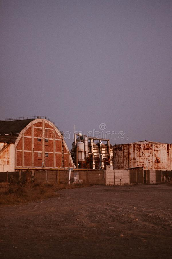 Vertical shot of old metal tanks near a barn with a clear sky in the background. A vertical shot of old metal tanks near a barn with a clear sky in the royalty free stock photography