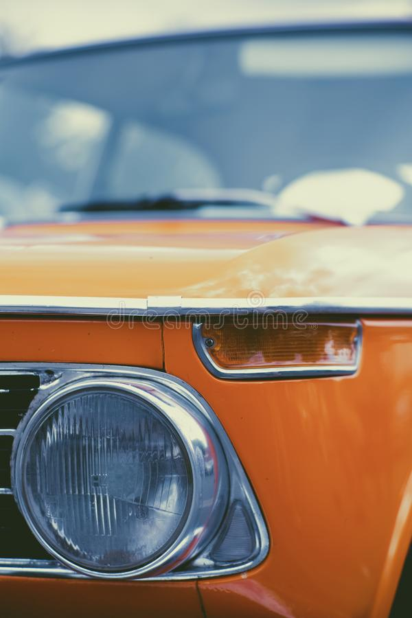 Vertical shot of an old orange car headlight with a blurred background royalty free stock photo