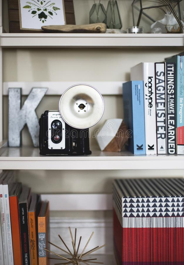 Vertical shot of an old photo camera on a bookshelf filled with books. A vertical shot of an old photo camera on a bookshelf filled with books stock image