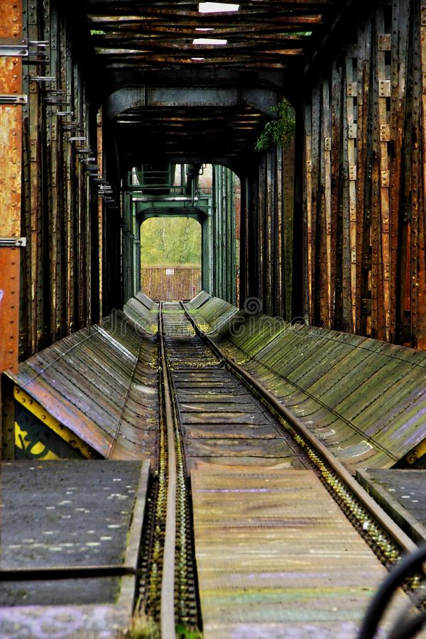 Vertical shot of an old rusty train track in a tunnel during daytime. A vertical shot of an old rusty train track in a tunnel during daytime stock images