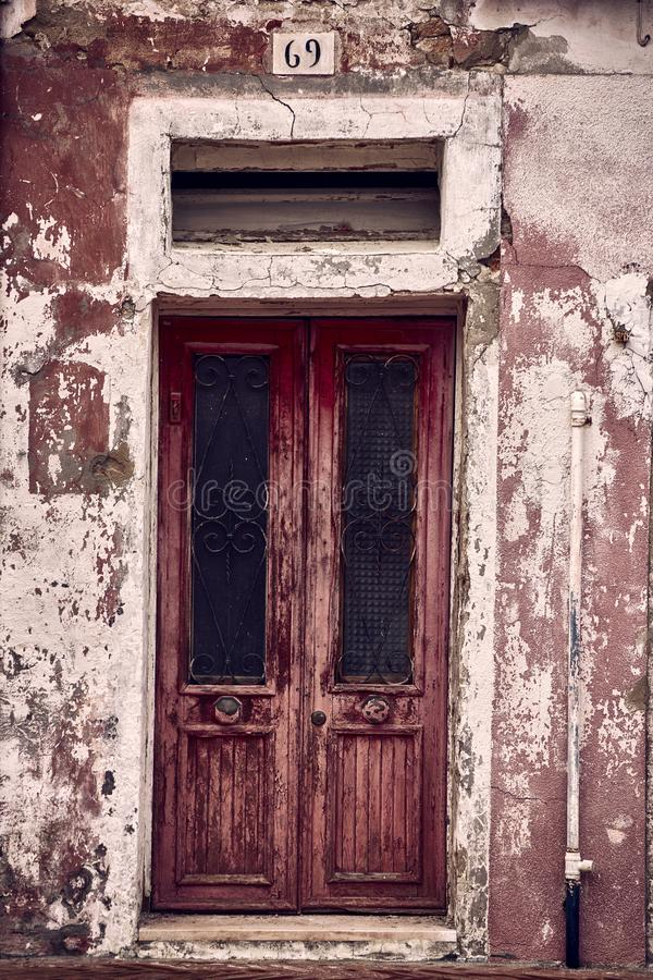 Vertical shot of an old wooden rusty weathered door of an abandoned office with grungy walls around stock photography