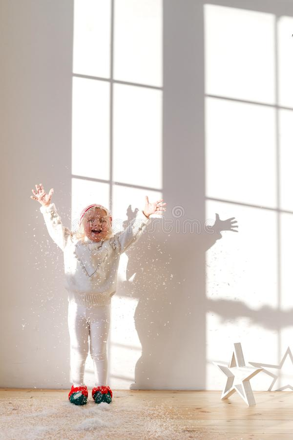 Vertical shot of overjoyed small girl dressed in white sweater and leggins, wears elf s shoes, plays with artificial royalty free stock photos