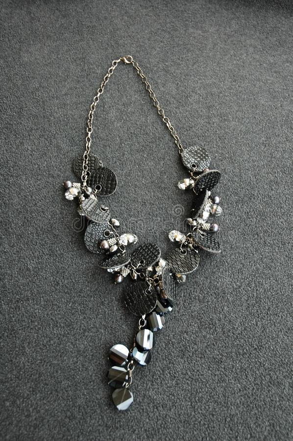 Vertical shot of a pendant necklace made of black and gray beads on a gray surface. A vertical shot of a pendant necklace made of black and gray beads on a gray stock photography