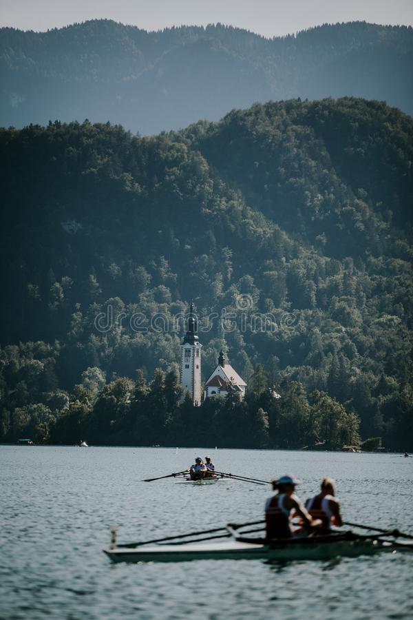 Vertical shot of people riding boats on the water with a building surrounded by trees. A vertical shot of people riding boats on the water with a building royalty free stock photos