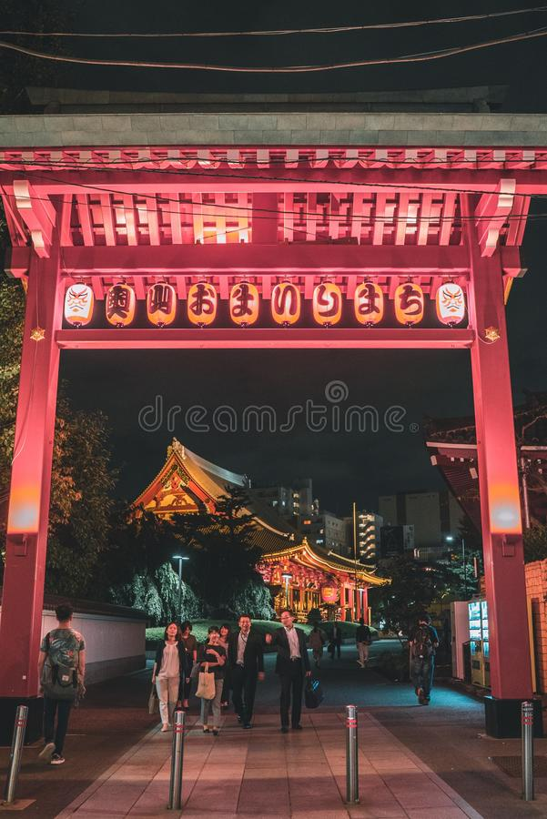 Vertical shot of people walking under a pink Shinto shrine in Tokyo, Japan during nighttime. A vertical shot of people walking under a pink Shinto shrine in royalty free stock photos