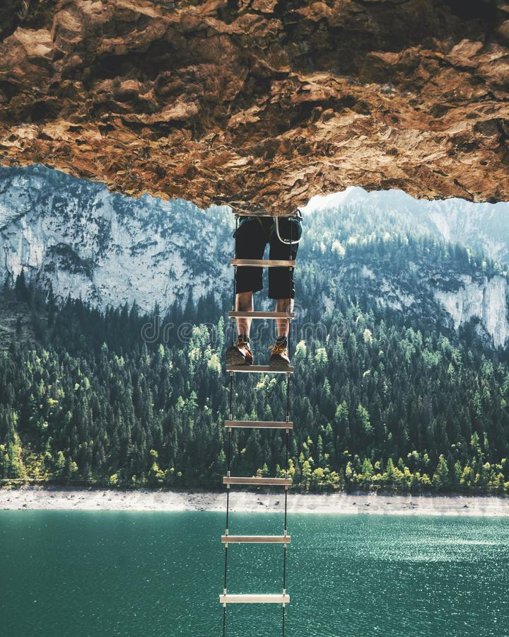 Vertical shot of a person climbing up a ladder hanging from a cliff. A vertical shot of a person climbing up a ladder hanging from a cliff with a forested stock photo