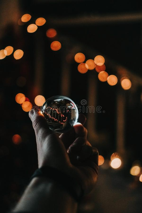 Vertical shot of a person holding a crystal ball with a bokeh background. A vertical shot of a person holding a crystal ball with a bokeh background royalty free stock image