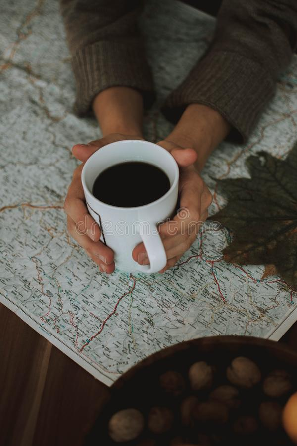 Vertical shot of a person holding a cup of black coffee on an area map shot from above. A vertical shot of a person holding a cup of black coffee on an area map stock photo