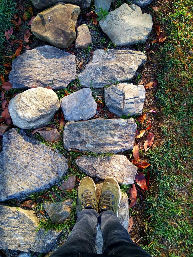 Vertical shot of person`s feet on a rocky pathway in a near grassy field royalty free stock photography