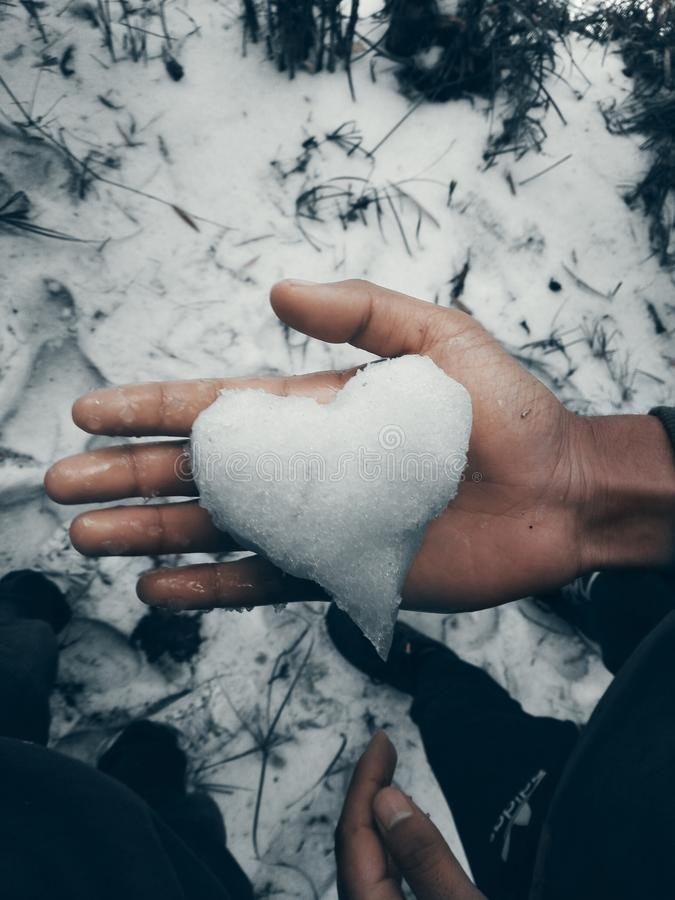 Vertical shot of a person`s hand holding a heart shaped snow with a blurred background. A vertical shot of a person`s hand holding a heart shaped snow with a royalty free stock photos