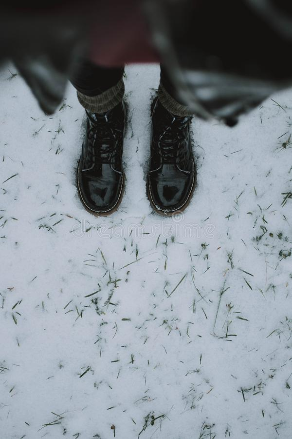 Vertical shot of a person wearing black boots standing on snow shot from above. A vertical shot of a person wearing black boots standing on snow shot from above royalty free stock image