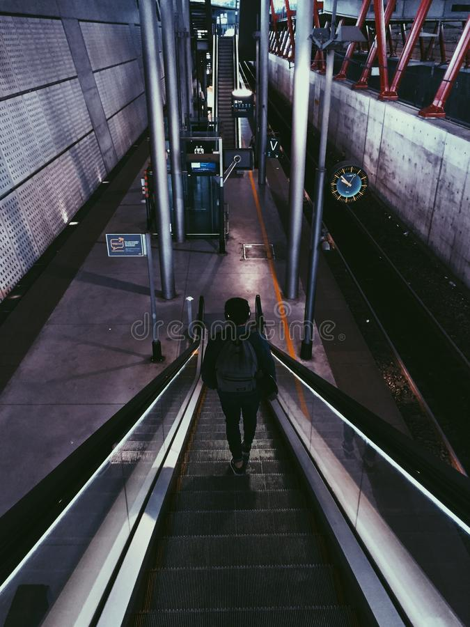 Vertical shot of a person wearing headphones and a backpack riding an escalator in a train station. A vertical shot of a person wearing headphones and a backpack stock photography