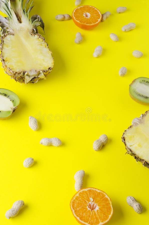 Vertical shot of pineapple,orange,kiwi fruit and peanuts in shell on yellow bright background. Top view of ripe fruits, unpeeled peanuts on bright yellow surface stock images