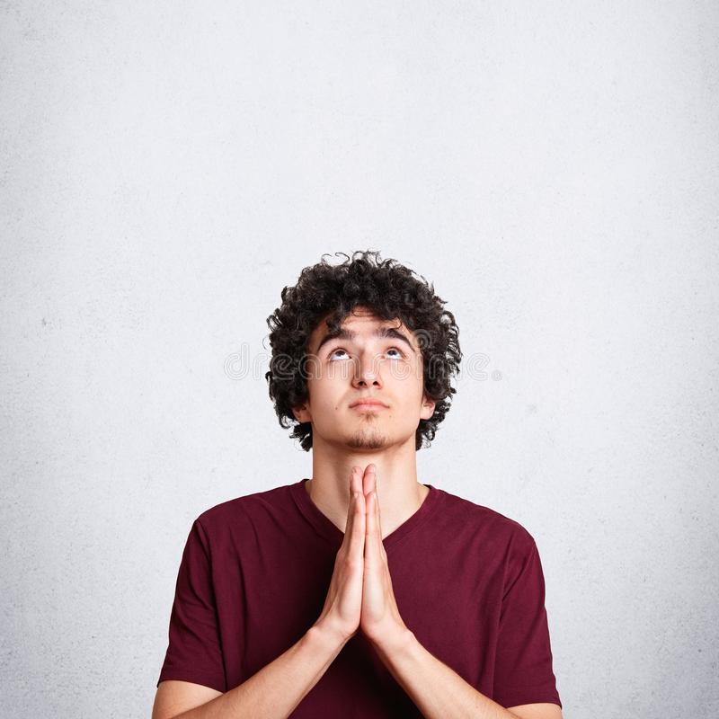 Vertical shot of pleasant looking miserable male prays for something, looks upwards with great hope, asks for health, poses agains. T white background with blank stock photo