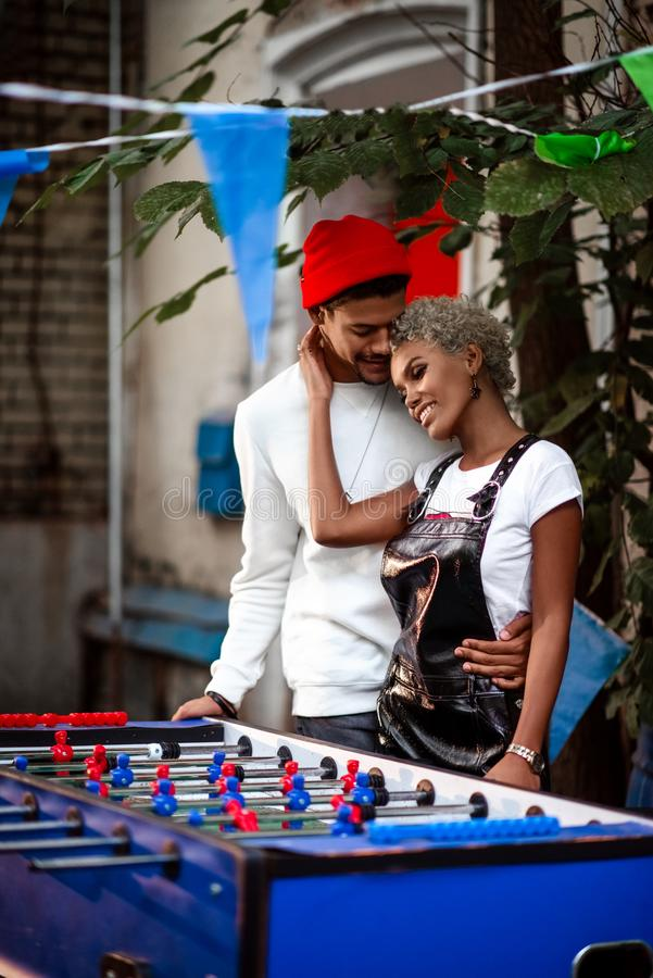 Vertical shot of pleasant looking mixed race female and her boyfriend embrace each other, stand near table football game royalty free stock photos